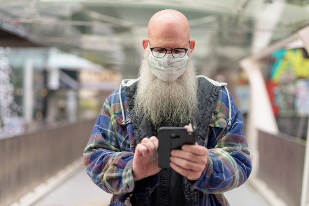 Mature bald bearded man with mask using phone in the city