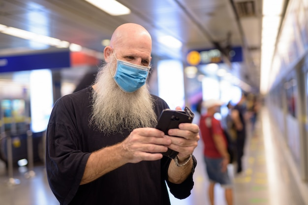 Mature bald bearded man with mask using phone at the subway train station