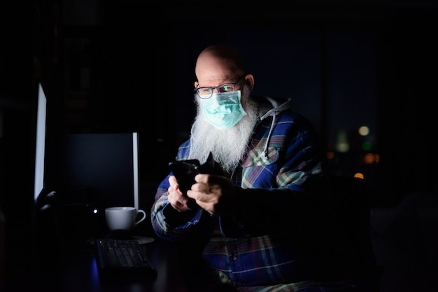 Mature bald bearded man with mask using phone while working from home late at night