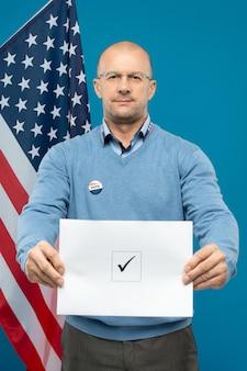 Зрелый лысый бизнесмен в очках и синем пуловере показывает вам свой избирательный бюллетень с галочкой в квадрате, стоя против флага сша