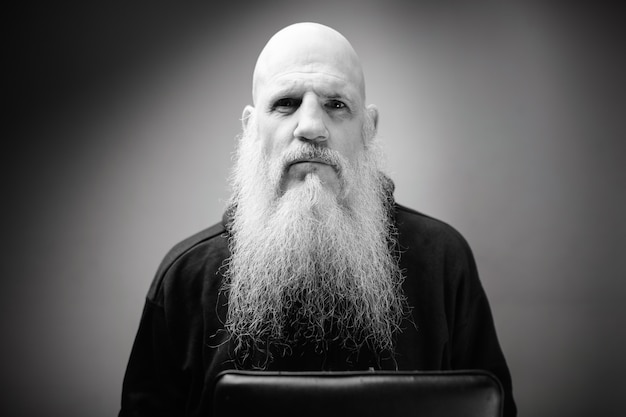 Зрелый лысый мужчина с длинной седой бородой у белой стены в черно-белом