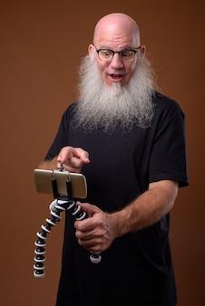 Mature bald man with long gray beard on brown