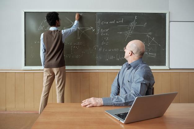 Зрелый лысый профессор сидит за столом и смотрит на студента, стоящего у доски, рисует график и объясняет свои действия на уроке