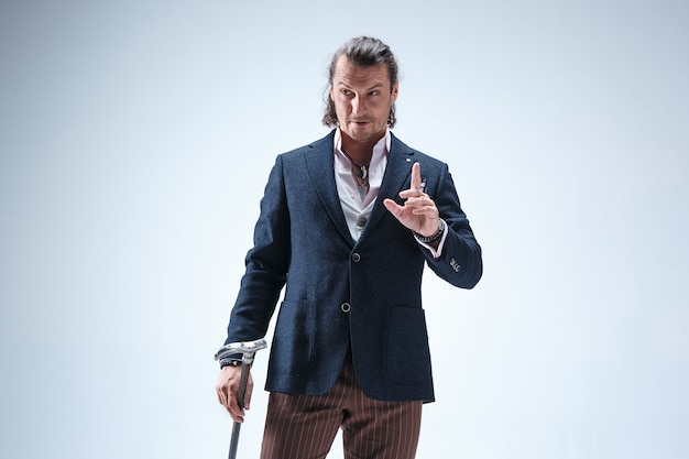 The mature barded man in a suit holding cane.