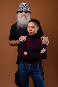 Зрелый бородатый лысый мужчина с молодой азиатской трансгендерной женщиной