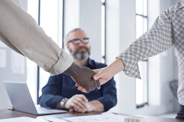 Зрелый бородатый бизнесмен сидит на своем рабочем месте и смотрит, как его коллеги пожимают руки во время встречи
