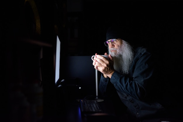Mature bearded hipster man drinking coffee while working overtime at home late at night in the dark