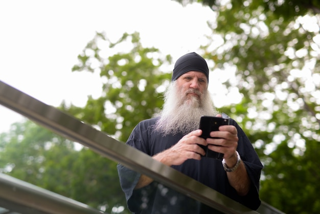 Mature bearded hipster man looking serious while using phone outside the subway train station