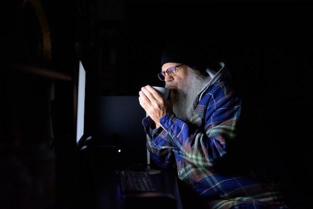 어둠 속에서 집에서 초과 근무를하는 동안 안경을 마시는 커피와 성숙한 수염 힙 스터 남자