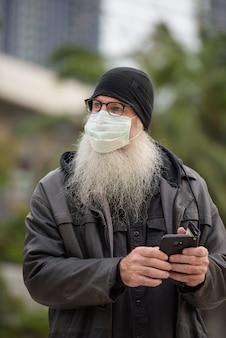 成熟したひげを生やしたヒップスター男マスク屋外で電話を使用しながら思考