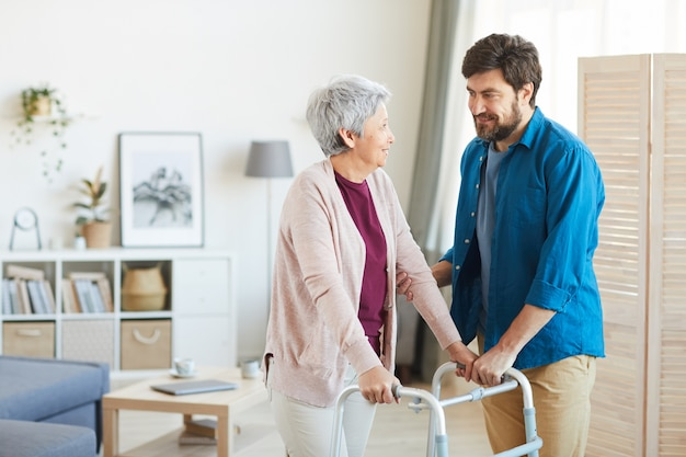 Mature bearded man caring about senior woman he helping her to walk around the room