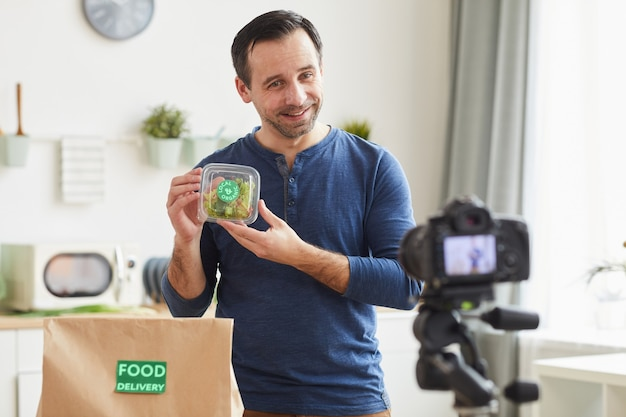 Mature bearded man holding organic salad box while recording food delivery service review in kitchen interior