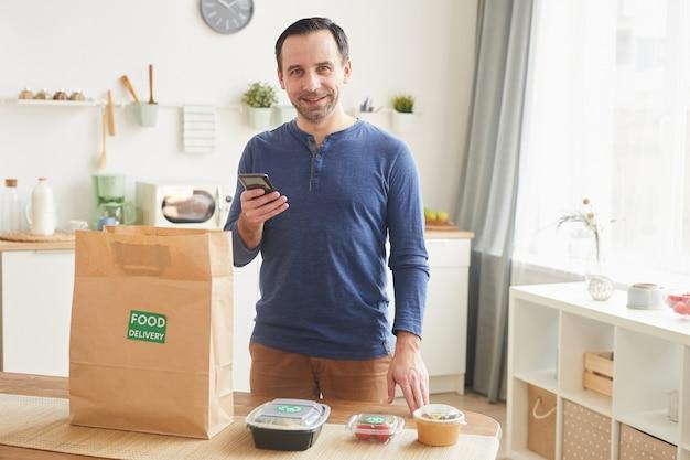 Зрелый бородатый мужчина улыбается и держит смартфон, распаковывая сумку для доставки еды в интерьере кухни