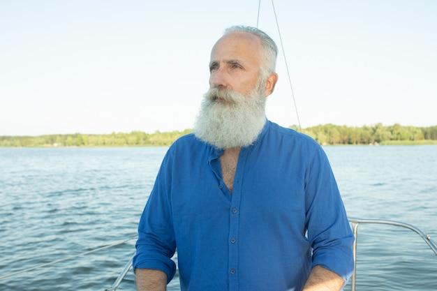Зрелый бородатый человек стоял у руля яхты на озере, рулевого управления, улыбаясь. l