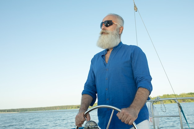 Mature bearded man standing at helm of yacht out at lake, steering, smiling.  l