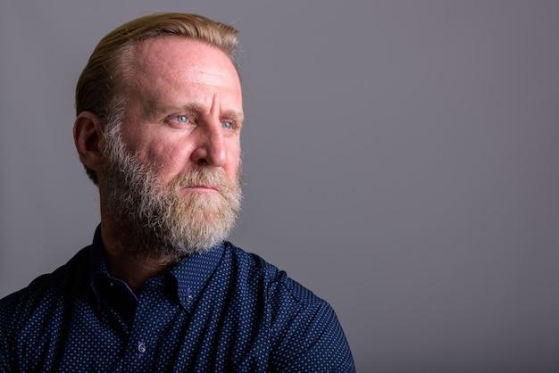 Зрелый бородатый мужчина думает