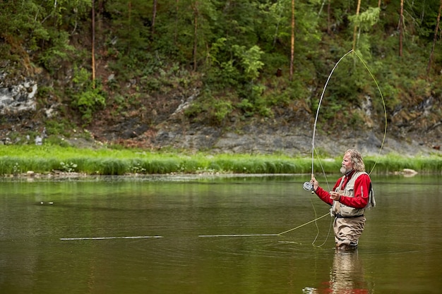 Mature bearded man in waterproof clothing in standing in river in forest while fly-fishing.