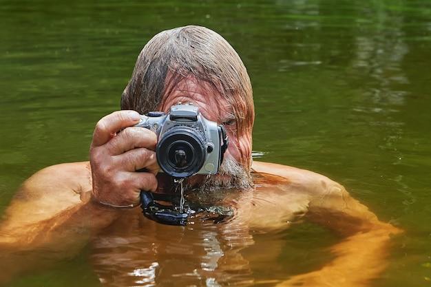 手に防水カメラを持った成熟したひげを生やした男は、川で泳いでいる間に写真を撮っています。
