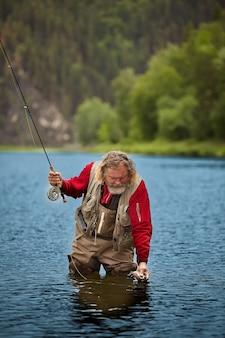 成熟したひげを生やした濡れた男は、フライフィッシングで釣った魚を見ていて、防水服を着ています。