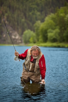 Mature bearded wet man is watching at fish, which he has caught by fly-fishing, he is in waterproof clothing.