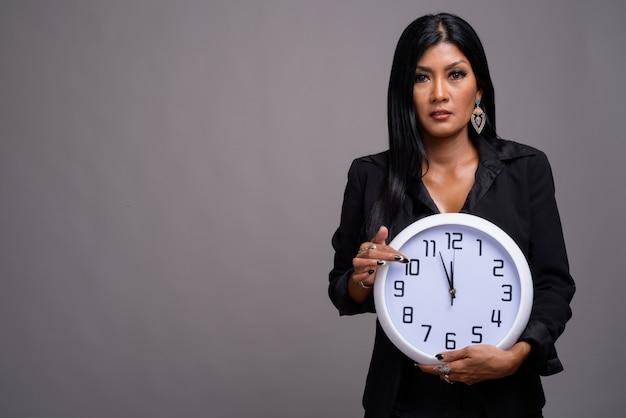 灰色の背景に対して成熟した美しいアジア女性実業家