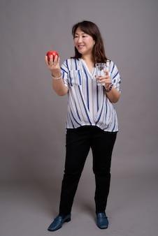 リンゴとガラスを保持している成熟した美しいアジア女性実業家