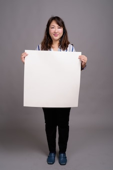 Mature beautiful asian businesswoman holding blank sign