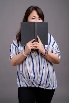 Зрелая красивая азиатская деловая женщина держит книгу