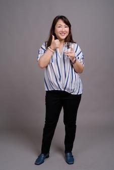 ガラスを保持している成熟した美しいアジア女性実業家