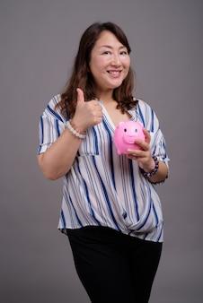 Зрелая красивая азиатская бизнес-леди держит копилку