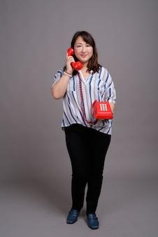 赤い電話を保持している成熟した美しいアジア女性実業家