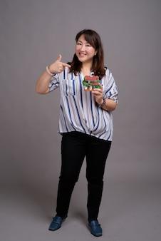 おもちゃの家を保持している成熟した美しいアジア女性実業家