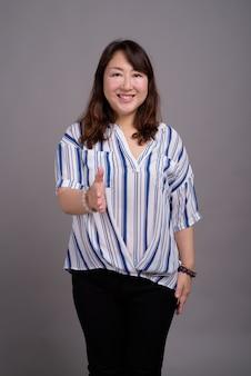 彼女の手を提供している成熟した美しいアジア女性実業家