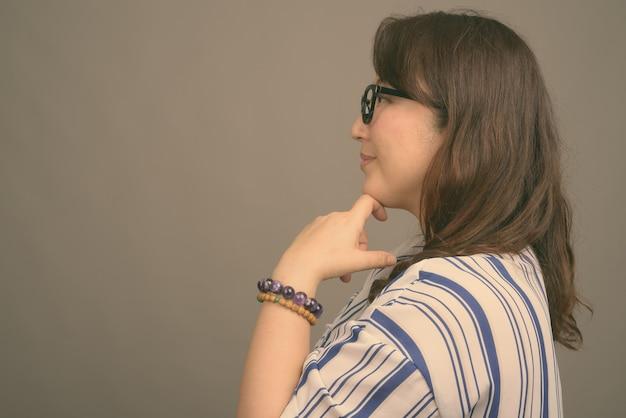 Зрелая красивая азиатская бизнес-леди в очках на сером
