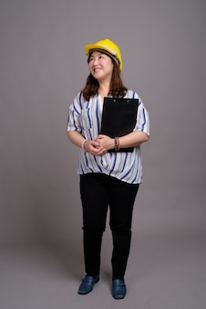 成熟した美しいアジア女性実業家のヘルメットを着用