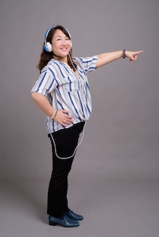 イヤホンで成熟した美しいアジア女性実業家