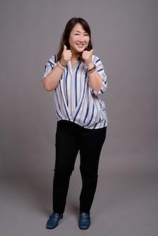 親指で成熟した美しいアジア女性実業家