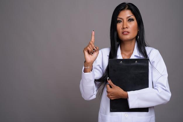 灰色の背景に対して成熟した美しいアジアの女性医師
