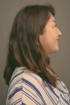 Зрелая красивая азиатская женщина на сером