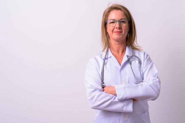 Зрелая красивая блондинка женщина врач против белого пространства