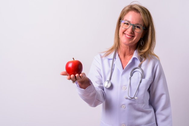 Mature beautiful blonde woman doctor against white space
