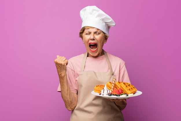 Mature beautiful old woman shouting aggressively, looking very angry, frustrated, outraged or annoyed, screaming no