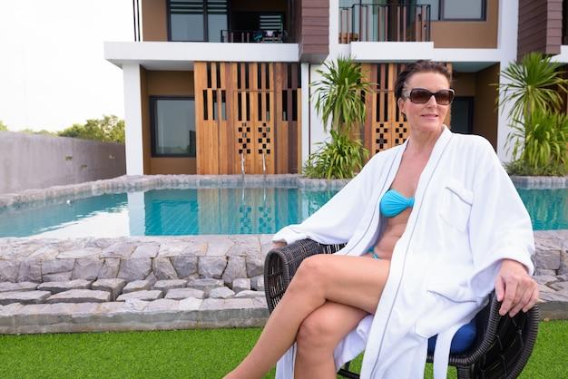 리조트 수영장 근처에 앉아 성숙한 아름다운 스칸디나비아 관광 여자