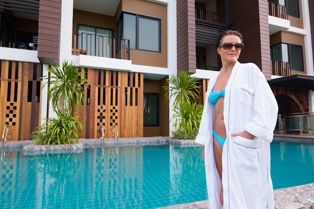 수영장 옆에 서있는 성숙한 아름다운 스칸디나비아 관광 여자