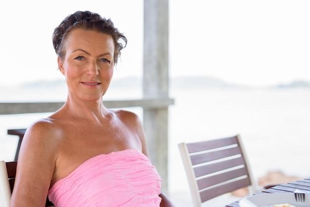 Зрелая красивая туристическая женщина на пляжном курорте