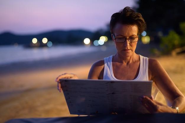 ビーチでリラックスした成熟した美しい観光女性