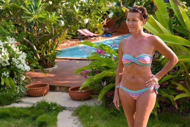 Зрелая красивая туристическая женщина в бикини на курорте