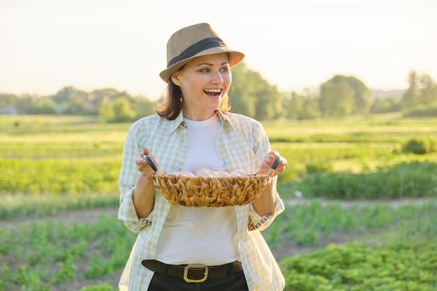 Mature beautiful woman farmer with basket of fresh eggs,