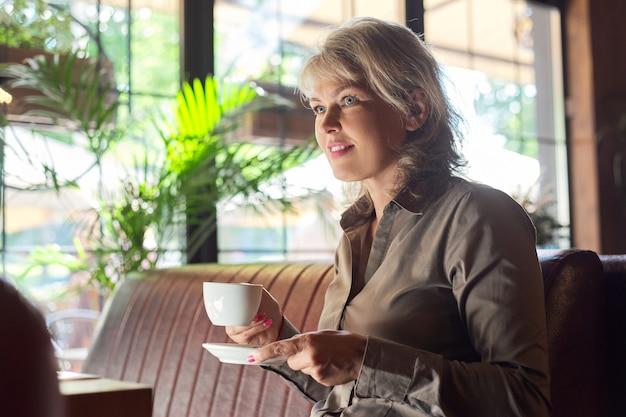Зрелая красивая женщина в ресторане с чашкой кофе. деловая женщина, отдыхающая во время перерыва, копией пространства