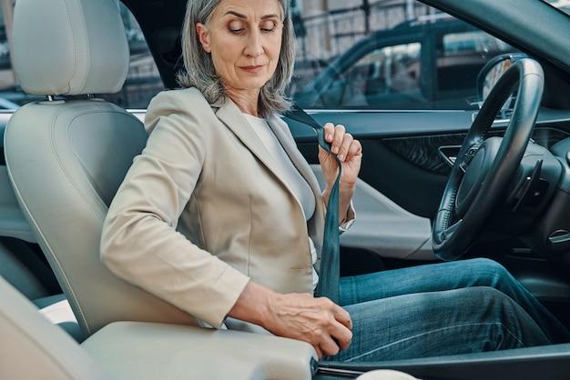Зрелая красивая женщина в элегантной повседневной одежде регулирует ремень безопасности